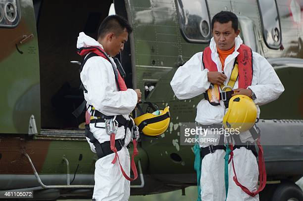 Members of an Indonesian search and rescue team coordinate operations prior to boarding an Indonesian Air Force Super Puma NAS332 helicopter to take...