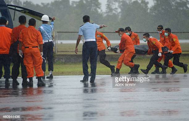 Members of an Indonesian search and rescue team transport the body of a victim from AirAsia flight QZ8501 recovered from the Java Sea in the rain at...