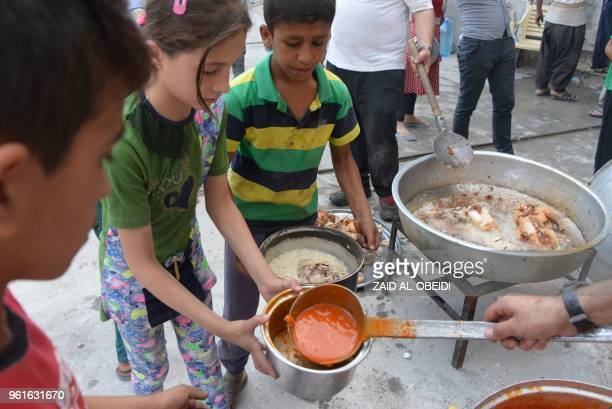 Members of an Iraqi charity organisation distribute food for Iftar the sunset meal that breaks the daytime fast to those in need during the holy...