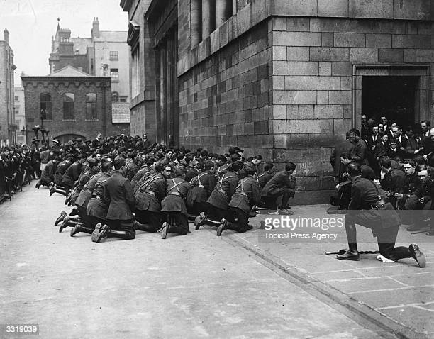 Members of an Irish National Army band kneeling in prayer at a special Requiem Mass at the Pro Cathedral Dublin on the first anniversary of the...