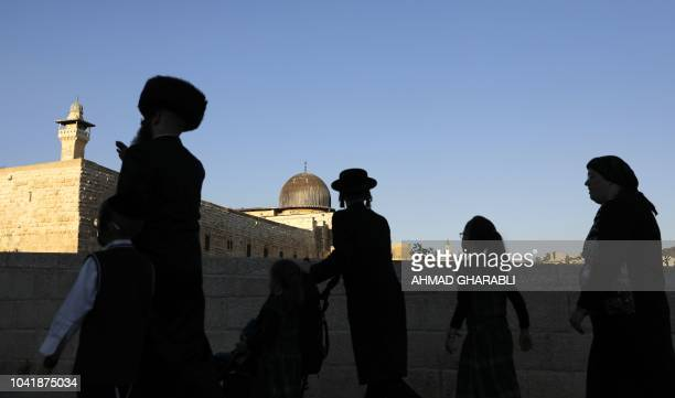 Members of an UltraOrthodox Jewish family walk at the Jewish quarter in Jerusalem's Old City overlooking alAqsa Mosque on September 27 2018 Comments...