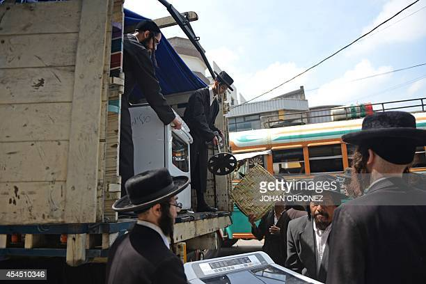 Members of an ultraOrthodox Jewish group unload their belongings from a truck as they arrive to the building where they will remain in Guatemala City...