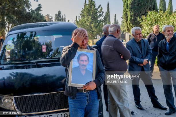Members of Asgerov family mourn at a cemetery for their five relatives who died when a rocket hit their home in the city of Ganja on October 17...
