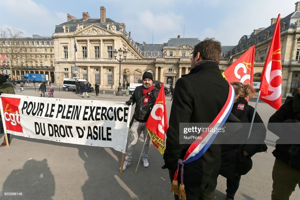 Members of associations rally to protest against a French bill relating to the right of asylum and immigration outside the Council of State, in Paris, on February 21, 2018. French President Emmanuel Macron's government is presenting its first big immigration bill, which human rights organizations criticize as repressive toward asylum-seekers. The plan will reduce the period of application for asylum to six months maximum, down from about one year including appeal.