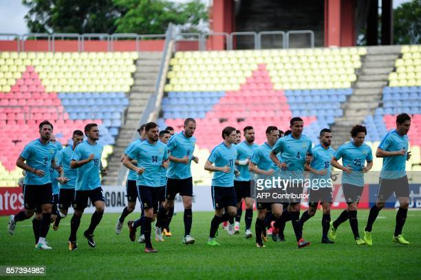 Members of Australia's national football team warm up during an official training session a day ahead of the 2018 World Cup qualifying football match...