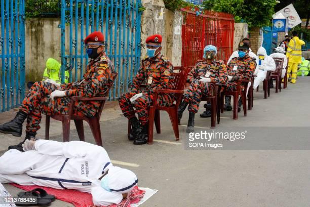 Members of Bangladesh fire brigade wearing face masks as a precaution while waiting in queue for the test. Bangabandhu Sheikh Mujib Medical...