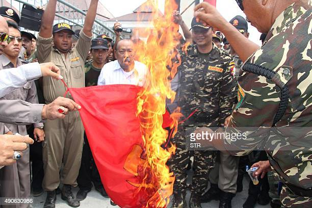 Members of Banser the youth wing of Indonesias largest Muslim organization Nahdlatul Ulama burn a communist flag in Blitar city located in eastern...