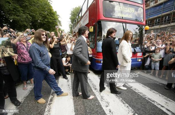 Members of Beatles tribute band 'Sgt Pepper's Only Dart Board Band' cross the famous Zebra crossing outside Abbey Road Studios in St John's Wood...