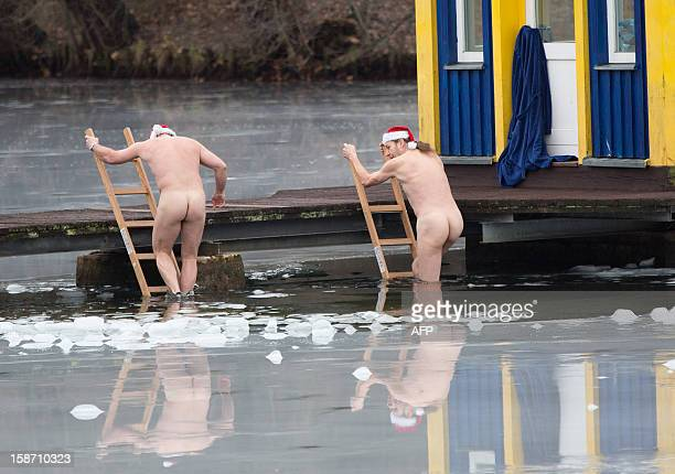 Members of Berlin's swimming club 'Berliner Seehunde' take a dip in the Orankesee lake during their traditional Christmas ice swimming session in...