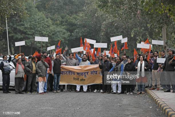Members of Bhatiya Majdoor Sangh hold placards and flags during their protest against terror attack in Pulwama district at Ashok Hotel on February 16...