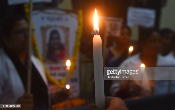 Members of Bihar Veterinary Association hold placards during a candle march seeking justice for the Hyderabad rape-murder case, at Museum road, on...