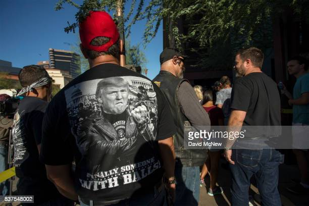 Members of Bikers for Trump stand guard next to a line of people entering a rally by President Donald Trump at the Phoenix Convention Center on...