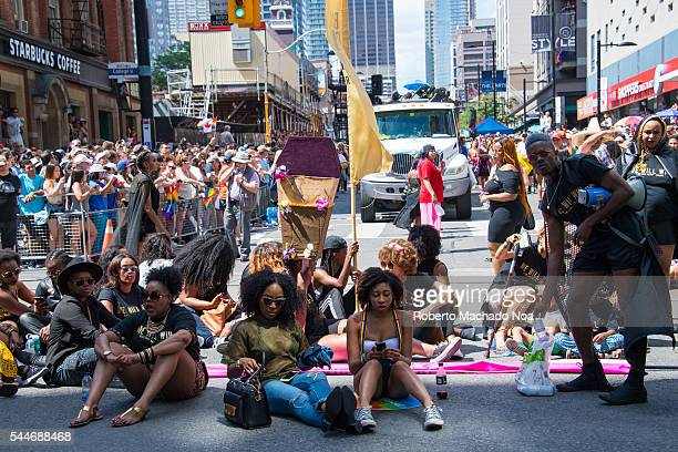 Members of Black Lives Matter sit and block the Pride Parade from the normal parade route