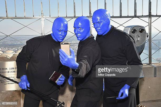 Members of Blue Man Group pose for a selfie as the Blue Man Group Lights The Empire State In Celebration Of Their 25th Anniversaryat The Empire State...