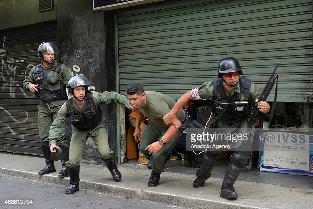 Members of Bolivarian National Guard rescue an aviation officer from a local store where he hid from the attacks of protesters during a protest...