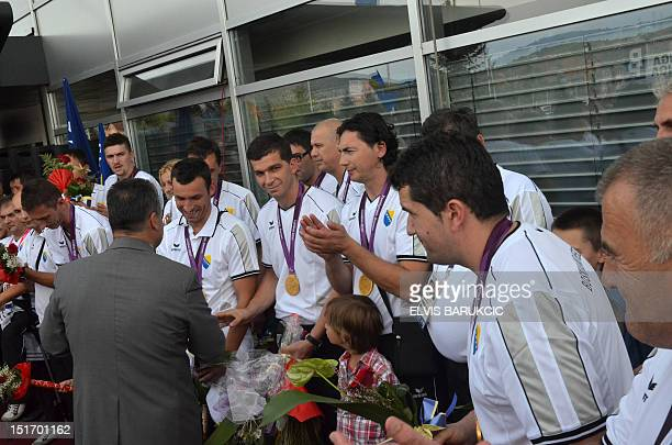 Members of Bosnia and Herzegovina's national para olympic volleyball team listen to their national anthem during a welcoming ceremony upon arrival at...