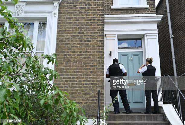 Members of Britain's Metropolitan Police force knock at the front door of the home of Number 10 Downing Street special advisor Dominic Cummings in...