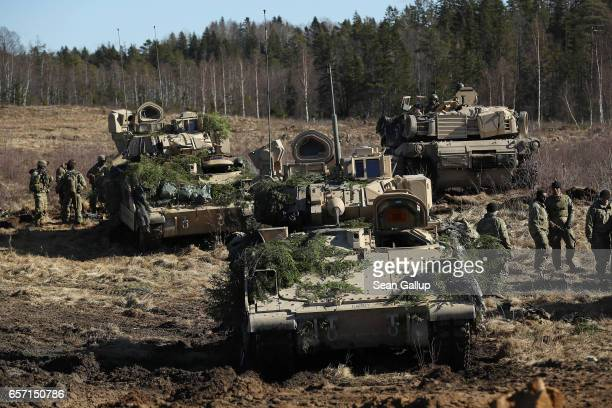 Members of Chaos Company 168 Armor Battalion of the 3rd Brigade Combat Team 4th Infantry Division stand near their M2A3 Bradley fighting vehicles and...
