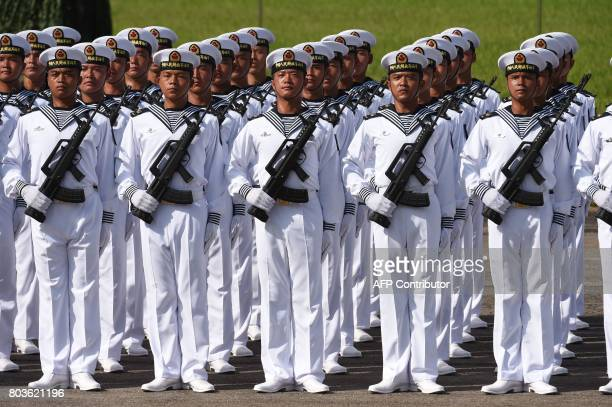 CORRECTION Members of Chinese People's Liberation Army based at the Hong Kong garrison prepare to parade prior to the arrival of Chinese President Xi...