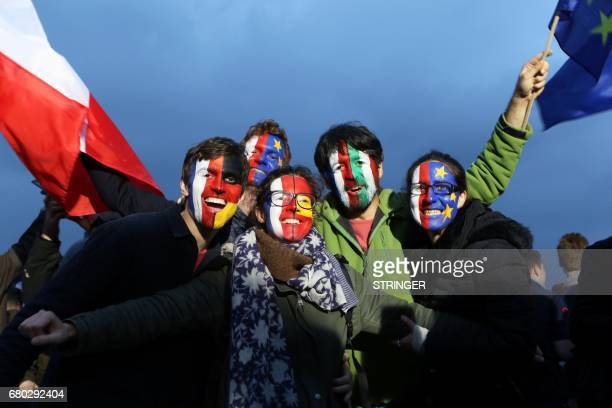 Members of civic organization Avaaz with their faces painted in the French German Italian Spanish and EU flags gather with other supporters of French...