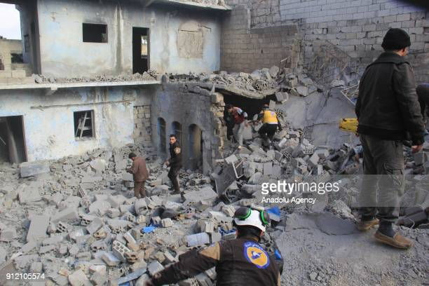 Members of civil defense carry out a search and rescue operation after an airstrike in the deescalation zone of Eriha district of Idlib Syria on...
