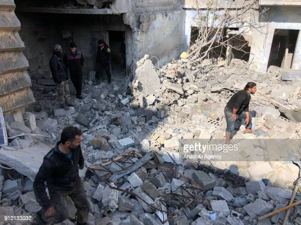 Members of civil defense carry out a search and rescue operation after an airstrike at a marketplace in the deescalation zone of Eriha district of...