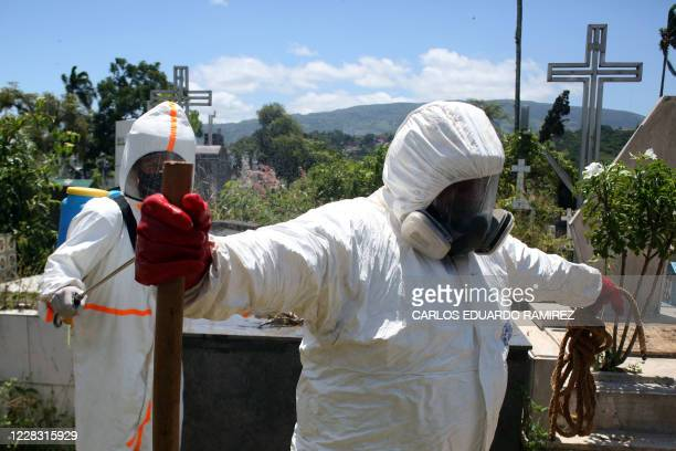 Members of Civil Protection disinfect themselves after the burial of an alleged COVID19 victim at the Municipal cemetery in San Cristobal Venezuela...