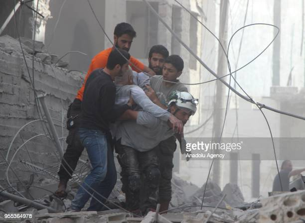 Members of civil right defense conduct a search and rescue operation on destroyed buildings after an airstrike was carried out over the city of Jisr...