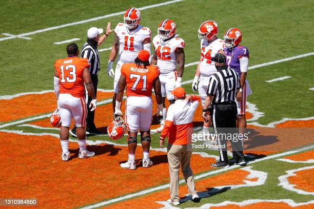 Members of Clemson's orange and white teams meet at midfield for the coin toss during the Clemson Orange and White Spring Game at Memorial Stadium on...