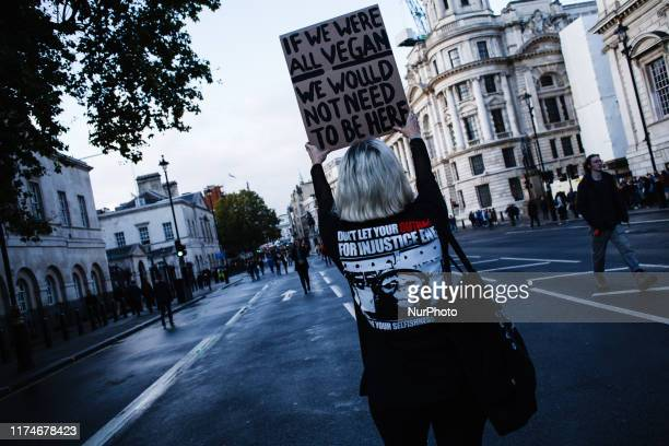 A members of climate change activist group Extinction Rebellion holds a placard calling for people to become vegan as she walks along Whitehall on...