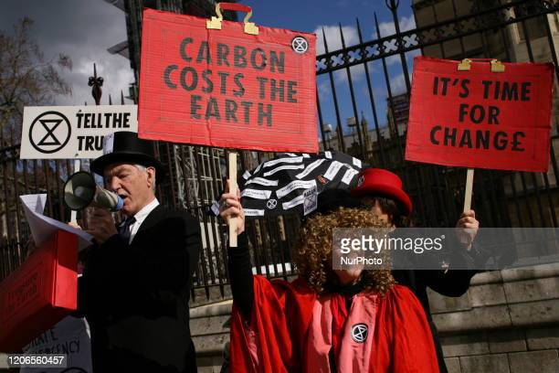 Members of climate change activist movement Extinction Rebellion stage a budget day demonstration outside the Houses of Parliament in London England...