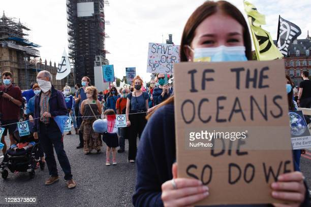 Members of climate change activist movement Extinction Rebellion, protesting against ecological destruction of the world's oceans, march across...
