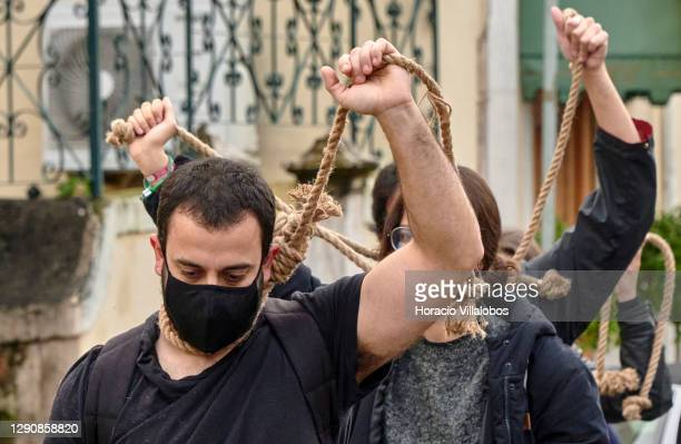 Members of Climaximo movement wear protective masks while pulling a noose as they arrive to stage a protest for the failure of the Paris Agreement to...