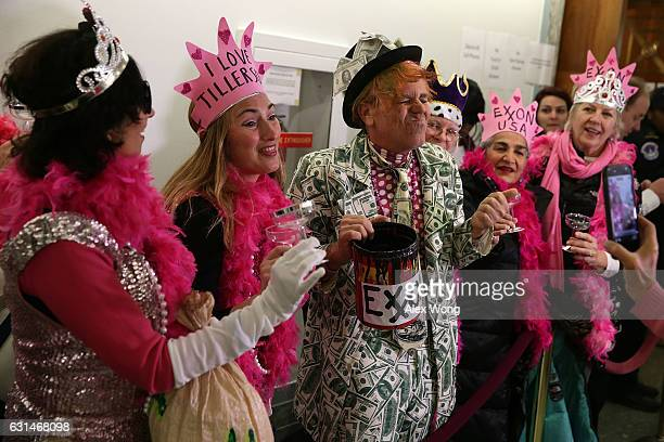 Members of CodePink stage a protest as they wait inline to enter the confirmation hearing of Former ExxonMobil CEO Rex Tillerson US Presidentelect...