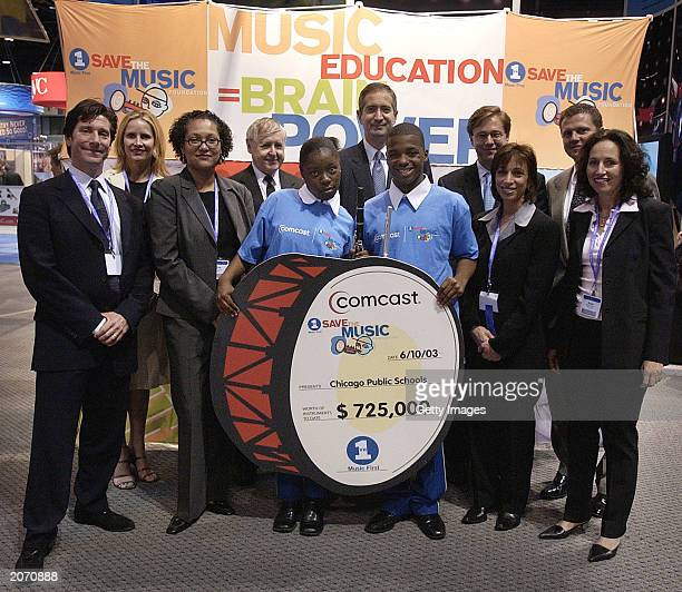 Members of Comcast and VH1 'Save the Music' stand with a check that represents their donation to date to the Chicago Public Schools music programs...