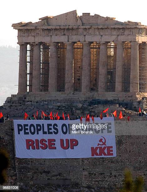 Members of Communist Party of Greece wave flags from the Acropolis Hill and display large banners from the front Parthenon Temple on May 4 2010 in...