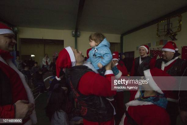 Members of Condor Motorcycle Club wearing Santa Claus clothes deliver new year gifts for abandoned children after they rode motorcycles around the...