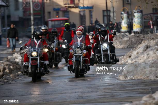 Members of Condor Motorcycle Club wearing Santa Claus clothes ride motorcycles around the city as they gather to deliver new year gifts for abandoned...