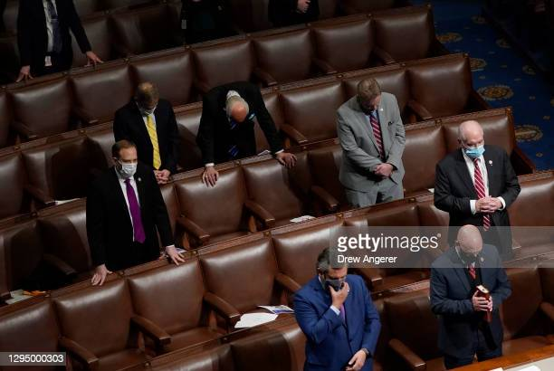 Members of congress look on as the final electoral votes are counted in the House Chamber during a reconvening of a joint session of Congress on...
