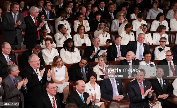 Members of congress react as US President Donald Trump addresses a joint session of the US Congress on February 28 2017 in the House chamber of the...