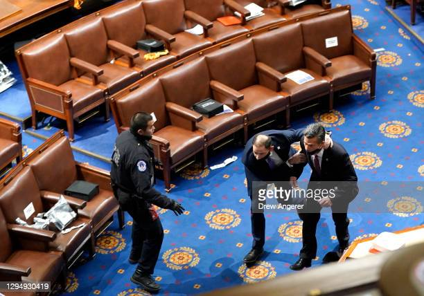 Members of congress run for cover as protesters try to enter the House Chamber during a joint session of Congress on January 06, 2021 in Washington,...