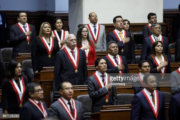 Members of congress stand for the national anthem during Martin Vizcarra Peru's president not pictured swearing in ceremony in Lima Peru on Friday...