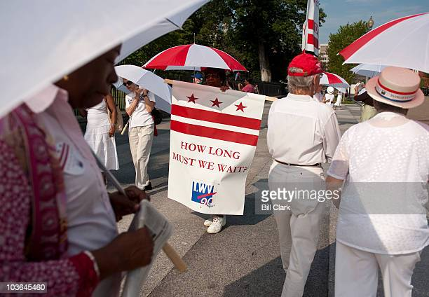 Members of D.C. Vote and the League of Women Voters march in front of the White House on Thursday, Aug. 26 to mark the 90th anniversary of the 19th...