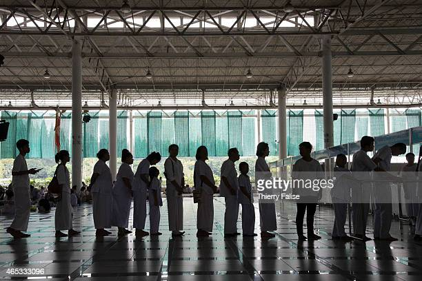 Members of Dhammakaya temple are queuing to get food during Magha Puja day, one of the main Buddhist celebrations. Dhammakaya temple, one of the...