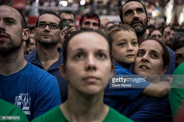 Members of different colles look at the colla 'Castellers de Vilafranca' as they build a human tower during the 26th Tarragona Competition on October...