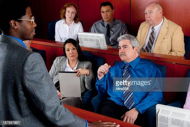 Members of diverse jury listening to an attorney in courtroom