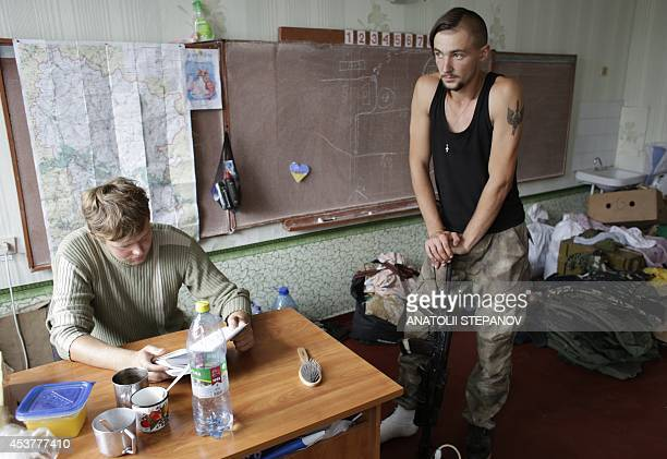Members of Donbass battalion a volunteer militia group devoted to ensuring a united Ukraine stand in a school converted into a baseon August 18 2014...