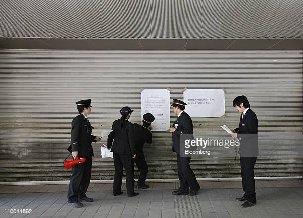 Members of East Japan Railways Co station staff work in front of a closed entrance of a train station after Tokyo Electric Co announced the power...
