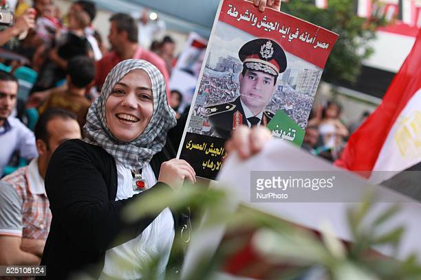 Members of Egyptian community in the Gaza Strip hold Egyptian flags and pictures of exarmy chief Abdel Fattah alSisi as they celebrate after Sisi...