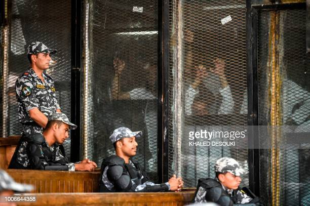 Members of Egypt's banned Muslim Brotherhood are seen inside a glass dock during their trial in the capital Cairo on July 28, 2018. - An Egyptian...